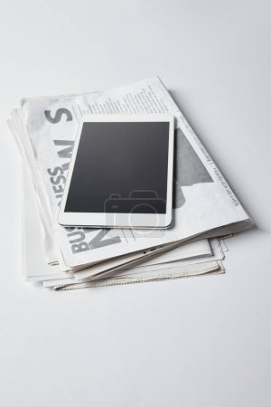 Photo for Digital tablet with blank screen on business newspapers on white - Royalty Free Image