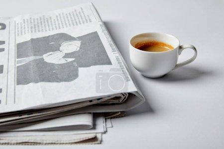 Photo pour Foyer sélectif de tasse avec café près des journaux sur blanc - image libre de droit