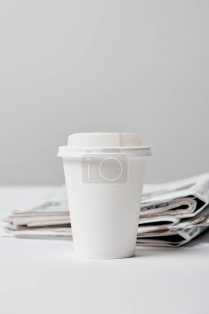 Photo for Selective focus of paper cup near newspapers on grey - Royalty Free Image