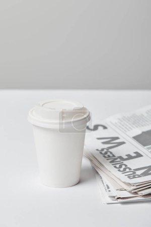 Photo pour Mise au point sélective de tasse de papier près de journaux d'affaires sur fond gris - image libre de droit