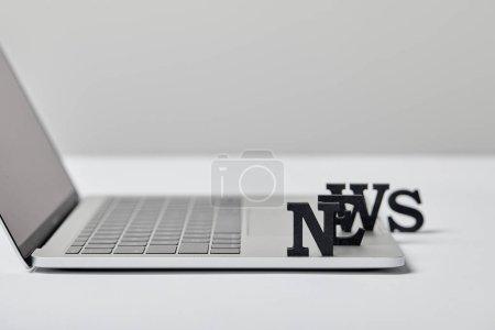 Photo pour Foyer sélectif des nouvelles lettrage près de l'ordinateur portable sur gris - image libre de droit