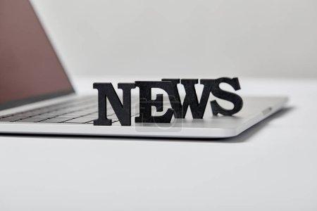 Photo pour Foyer sélectif de nouvelles noir lettrage près de l'ordinateur portable sur gris - image libre de droit