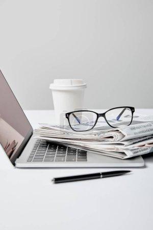 Photo pour Ordinateur portable avec écran vierge près des journaux, lunettes, stylo et tasse en papier sur gris - image libre de droit