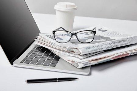 Foto de Enfoque selectivo de ordenador portátil con pantalla en blanco junto a la taza de periódicos, vidrios, papel y lápiz de negocios en blanco - Imagen libre de derechos