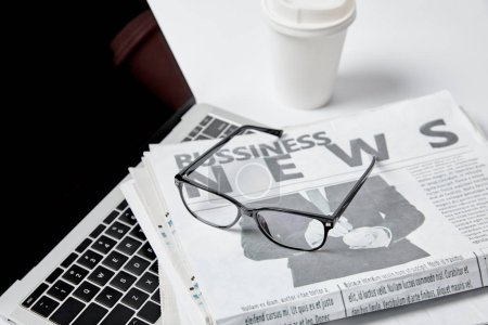 Photo for Laptop with blank screen near business newspapers, glasses, paper cup and pen on white - Royalty Free Image