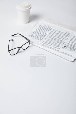 Photo for Glasses near paper cup and newspapers on white - Royalty Free Image