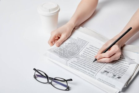 Photo for Cropped view of woman holding pencil near newspaper, glasses and paper cup on white - Royalty Free Image
