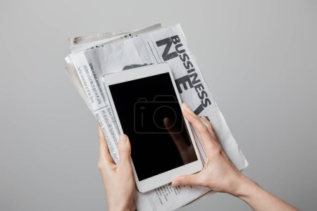 Photo for Cropped view of woman holding digital tablet with blank screen and business newspapers isolated on grey - Royalty Free Image