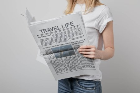 Photo for Cropped view of woman reading travel newspapers isolated on grey - Royalty Free Image