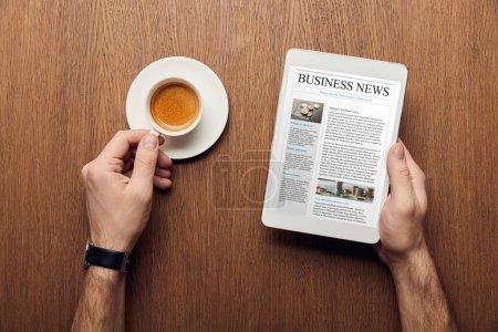 Photo pour Vue recadrée de l'homme tenant tablette numérique avec des nouvelles d'affaires à l'écran et tasse de café - image libre de droit
