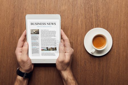 top view of man holding digital tablet with business news on screen near cup of coffee