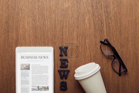 Photo for Top view of digital tablet with business news on screen near news lettering, glasses and paper cup - Royalty Free Image