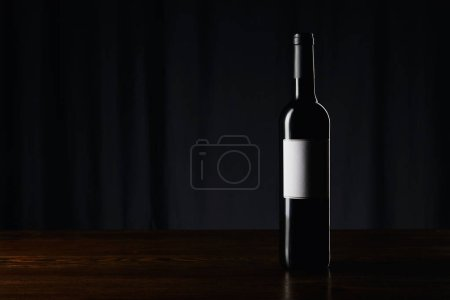 Photo pour Bouteille de vin avec étiquette vierge sur une surface en bois sombre - image libre de droit