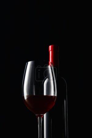 Photo pour Bouteille et verre de vin rouge isolé sur fond noir - image libre de droit