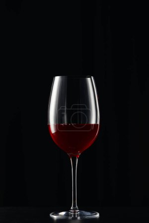 Photo for Glass with red wine on dark surface isolated on black - Royalty Free Image
