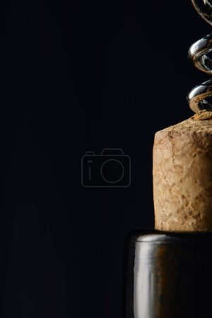 Photo for Close up of wine bottle with wooden cork and steel corkscrew isolated on black - Royalty Free Image