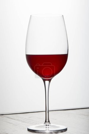Photo for Glass of red wine on dark surface on white - Royalty Free Image