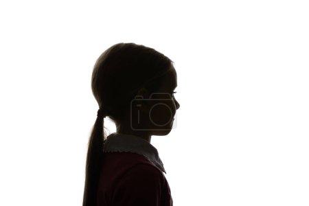 Silueta de niño con cola de caballo mirando hacia otro lado aislado en blanco