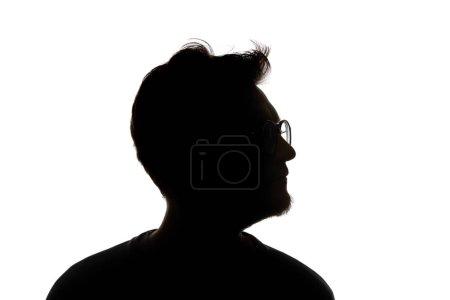 Silueta de hombre en gafas mirando hacia otro lado aislado sobre blanco