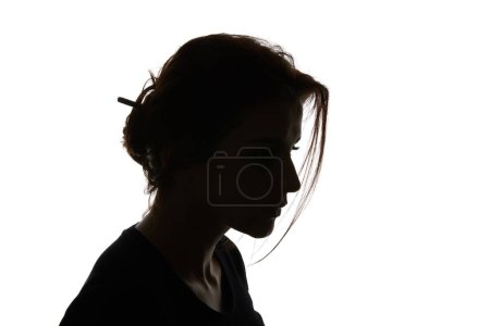 Silhouette of pensive woman looking down isolated on white