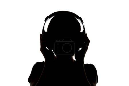 Photo pour Silhouette de fille dans le casque écoutant la musique dans le casque d'isolement sur le blanc - image libre de droit
