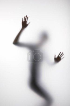 Silueta borrosa de persona tocando vidrio con las manos