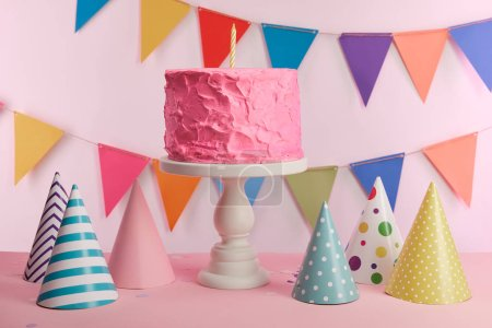delicious pink birthday cake with candle on cake stand near party caps and decoration