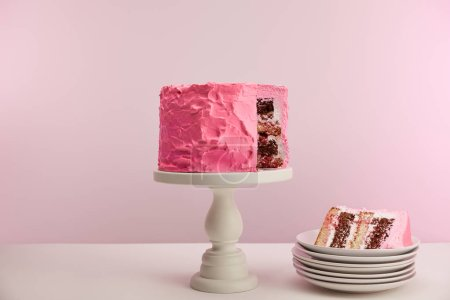 Photo for Piece of sweet pink birthday cake in white saucer on pink - Royalty Free Image