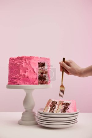 Photo for Cropped view of woman holding golden fork near piece of sweet birthday cake in white saucer on pink - Royalty Free Image