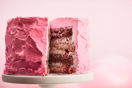 Photo for Close up of cut sweet birthday cake on cake stand on pink - Royalty Free Image