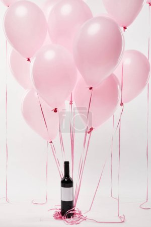 Photo for Pink air balloons with wine bottle isolated on white - Royalty Free Image