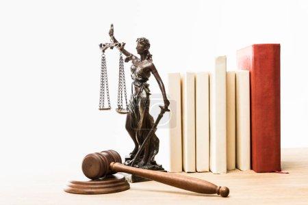 Photo pour Figurine avec les échelles de la justice, gavel brun et livres sur la table en bois isolé sur blanc - image libre de droit