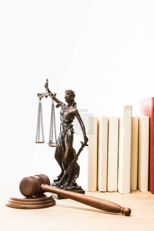 Photo for Metal figure with scales of justice, gavel and books on wooden table isolated on white - Royalty Free Image