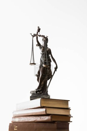Photo for Low angle view of bronze figurine with scales of justice on pile of brown books isolated on white - Royalty Free Image
