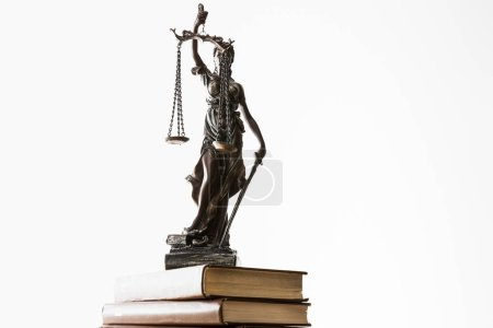 Photo for Bronze figurine with scales of justice on pile of brown books isolated on white - Royalty Free Image
