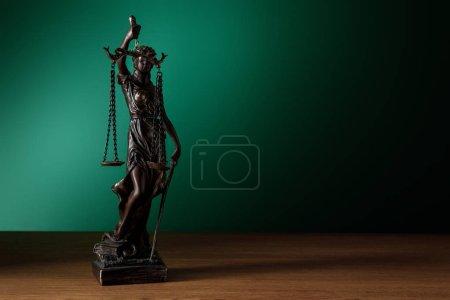 Photo pour Statuette en bronze avec des écailles de justice sur une surface en bois sur fond vert foncé - image libre de droit