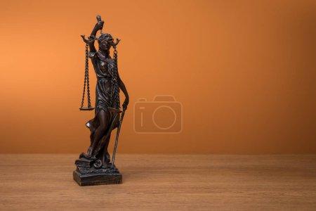 Photo pour Statuette en bronze avec la balance de la justice sur une table en bois sur fond orange - image libre de droit