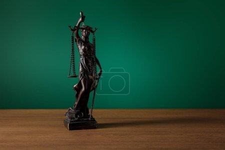 Photo pour Statuette en bronze avec écailles de justice sur table en bois sur fond vert foncé - image libre de droit