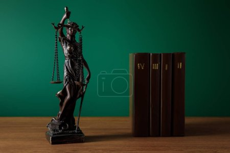 Photo for Bronze statuette with scales of justice and volumes of brown books on wooden table on dark green background - Royalty Free Image