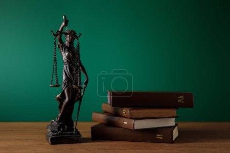 Photo pour Statuette en bronze avec écailles de justice et volumes de livres sur table en bois sur fond vert foncé - image libre de droit