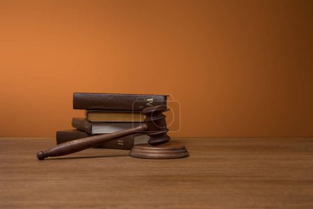 Photo pour Volumes de livres bruns dans des couvertures en cuir et marteau sur table en bois sur fond orange foncé - image libre de droit