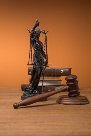 Photo pour Statuette en bronze avec écailles de justice, marteau et livres sur table en bois sur fond orange - image libre de droit