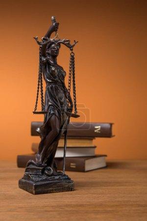 Photo pour Mise au point sélective de la statuette de bronze avec les échelles de la justice et de volumes de livres bruns sur table en bois - image libre de droit