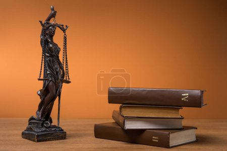 Photo pour Statuette en bronze avec la balance de la justice et de volumes de livres bruns sur table - image libre de droit