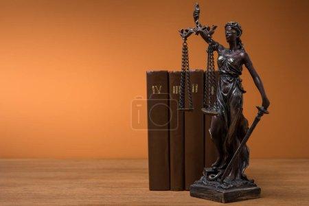 Photo pour Statuette en bronze avec les échelles de la justice et de la rangée de livres bruns sur table - image libre de droit