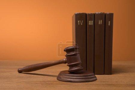 Photo pour Focus sélectif des volumes de livres bruns dans des couvertures en cuir et marteau sur table en bois - image libre de droit