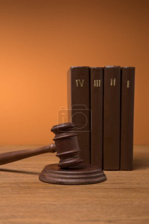 Photo for Volumes of brown books in leather covers and gavel on wooden table - Royalty Free Image