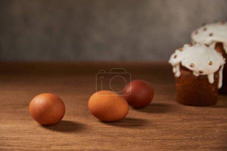 Foto de Enfoque selectivo de huevos de pollo pintados y pasteles de Pascua en la superficie de madera con espacio de copia - Imagen libre de derechos