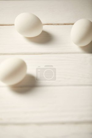 Photo for Selective focus of uncooked chicken eggs on white wooden planks with copy space - Royalty Free Image