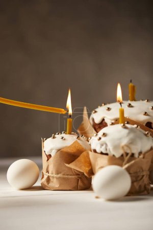 delicious easter cakes with burning candles and chicken eggs on white table